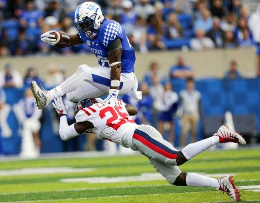 Kentucky running back Benny Snell Jr., top, leaps over Mississippi defensive back C.J. Moore during the first half of an NCAA college football game Saturday, Nov. 4, 2017, in Lexington, Ky.