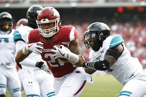 Arkansas running back Devwah Whaley pushes past Costal Carolina defender Eric Church, right, to score a touchdown during the first half of an NCAA college football game Saturday, Nov. 4, 2017, in Fayetteville, Ark.
