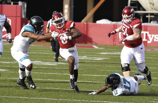 Arkansas running back T.J. Hammonds shakes Costal Carolina defenders Shane Johnson (9) and Anthony Chelsey (17) as he runs for a touchdown during the first half of an NCAA college football game Saturday, Nov. 4, 2017, in Fayetteville, Ark.