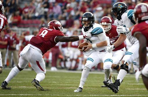 Arkansas linebacker De' Jon Harris, left, puts the pressure on Coastal Carolina quarterback Kilton Anderson during the second half of an NCAA college football game Saturday, Nov. 4, 2017, in Fayetteville, Ark.