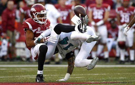 Arkansas receiver Deon Stewart, left, cannot hold onto the ball as he is hit by Coastal Carolina defender Preston Carey during the second half of an NCAA college football game Saturday, Nov. 4, 2017, in Fayetteville, Ark.