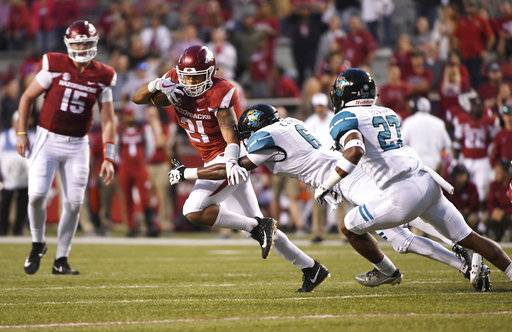 Arkansas running back Devwah Whaley (21) tries to shake Coastal Carolina defender Kerron Johnson as he runs for a gain during the second half of an NCAA college football game Saturday, Nov. 4, 2017, in Fayetteville, Ark.