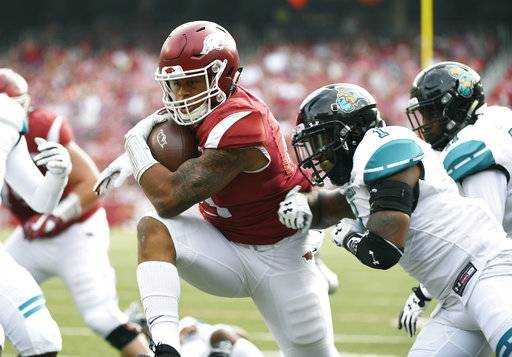 Arkansas running back Devwah Whaley, center, pushes past Costal Carolina defender Eric Church to score a touchdown during the first half of an NCAA college football game Saturday, Nov. 4, 2017, in Fayetteville, Ark.