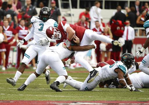 Arkansas quarterback Cole Kelley is tackled by Costal Carolina defender Shane Johnson during the first half of an NCAA college football game Saturday, Nov. 4, 2017, in Fayetteville, Ark.