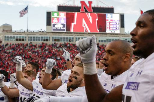 Northwestern players including running back Corey Acker, center, celebrate with fans their 31-24 win over Nebraska in overtime in an NCAA college football game in Lincoln, Neb., Saturday, Nov. 4, 2017.