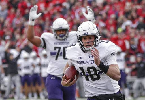 Northwestern offensive lineman Rashawn Slater (70) gestures touchdown as quarterback Clayton Thorson (18) runs for a touchdown during the second half of an NCAA college football game against Nebraska in Lincoln, Neb., Saturday, Nov. 4, 2017. Northwestern won 31-24 in overtime.