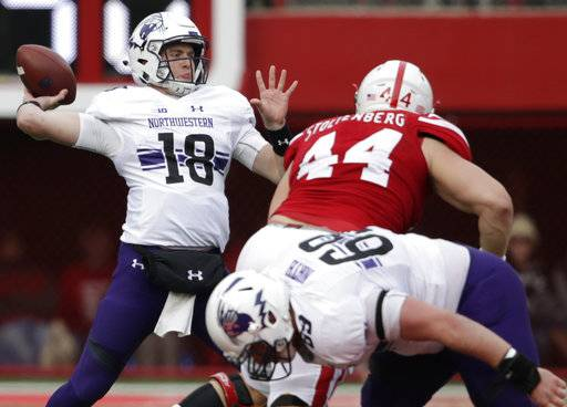 Northwestern quarterback Clayton Thorson (18) throws as offensive lineman Brad North (69) blocks Nebraska defensive lineman Mick Stoltenberg (44) during the first half of an NCAA college football game in Lincoln, Neb., Saturday, Nov. 4, 2017.