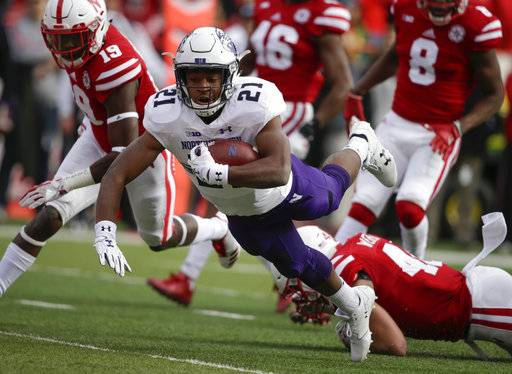Northwestern running back Justin Jackson (21) scores a touchdown as he is tackled by Nebraska defensive lineman Mick Stoltenberg (44) as defensive back Marquel Dismuke (19) runs left, during the first half of an NCAA college football game in Lincoln, Neb., Saturday, Nov. 4, 2017.