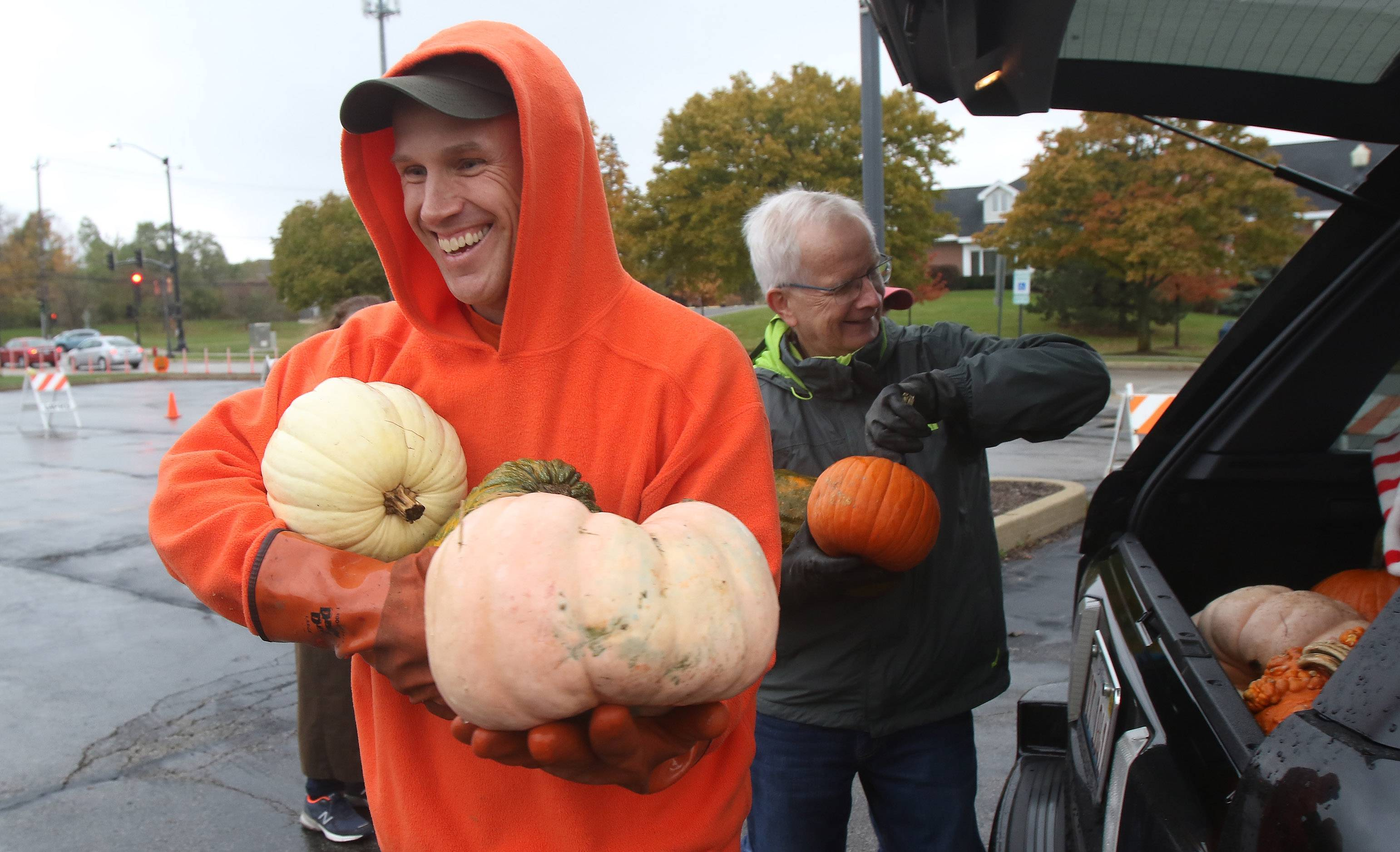 Composting specialist Vytas Pabedinskas of Grayslake, left, and Art Nelson of Lake Forest unload pumpkins from a car as they collected for composting at the Mundelein Community Center on Sunday. The traditional pumpkin roll and pumpkin catapult were canceled due to weather.