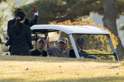 President Donald Trump, center,  waves as Japanese Prime Minister Shinzo Abe, right, and he finish playing golf at Kasumigaseki Country Club, Sunday, Nov. 5, 2017, in Kawagoe, Japan. Trump is on a five country trip through Asia traveling to Japan, South Korea, China, Vietnam and the Philippines.