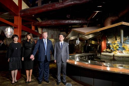 U.S. President Donald Trump, accompanied by first lady Melania Trump, second from left, Japanese Prime Minister Shinzo Abe, right, and his wife Akie Abe, speaks to members of the media before having dinner at Ginza Ukai Tei, Sunday, Nov. 5, 2017, in Tokyo. Trump is on a five-country trip through Asia traveling to Japan, South Korea, China, Vietnam and the Philippines.