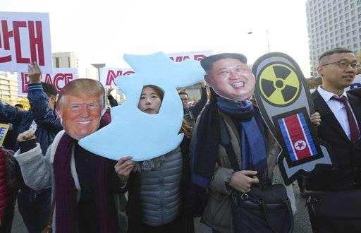 Anti-war protesters wearing cutouts of U.S. President Donald Trump and North Korean leader Kim Jong Un, right, march after a rally demanding peace of the Korean peninsula near U.S. Embassy in Seoul, South Korea, Sunday, Nov. 5, 2017. Trump will arrive in South Korea on Nov. 7 for a two-day visit to hold a summit with South Korean President Moon Jae-in.