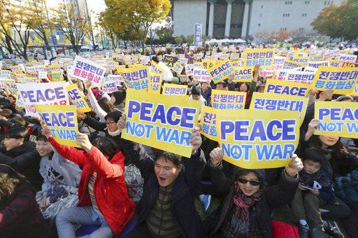 Ant-war protesters hold up their cards during a rally demanding peace of the Korean peninsula near U.S. Embassy in Seoul, South Korea, Sunday, Nov. 5, 2017. U.S. President Donald Trump will arrive in South Korea on Nov. 7 for a two-day visit to hold a summit with South Korean President Moon Jae-in.