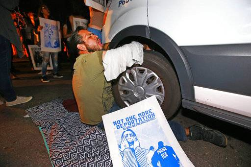 FILE - In this Feb. 8, 2017, file photo, a protester locked himself to the van carrying Guadalupe Garcia de Rayos that is stopped by protesters outside the Immigration and Customs Enforcement facility in Phoenix. The Trump administration has revamped a decade-old deterrence program for prosecuting immigrants in its get-tough approach to immigration. But it's unclear just how effective that program is. (Rob Schumacher/The Arizona Republic via AP, File)/The Arizona Republic via AP)