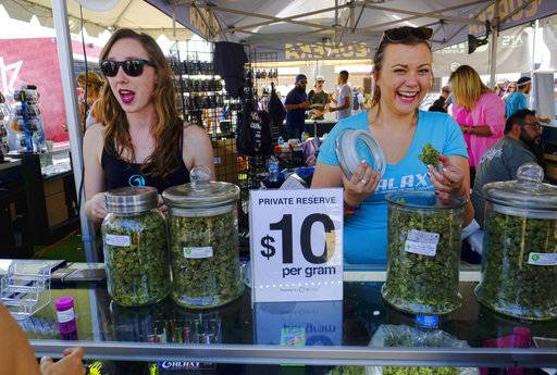 FILE - In this Sunday, April 23, 2017 file photo vendors offer marijuana for sale at the High Times Cannabis Cup in San Bernardino, Calif. Consumers eager for the coming of California's legal recreational marijuana market should be ready for sticker shock. An array of new taxes and fees will be attached to pot sales, driving up prices.
