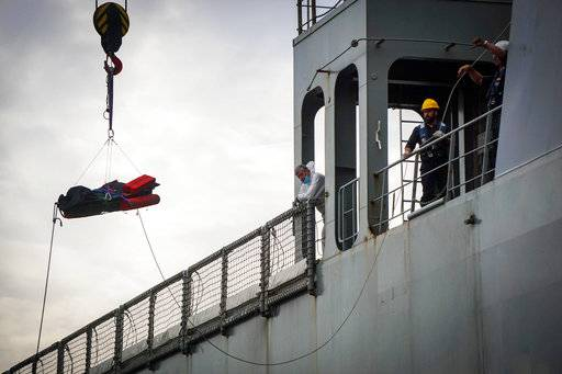 Rescuers recover a dead body from the Spanish ship 'Cantabria' in the harbour of Salerno, Italy, Sunday, Nov. 5 2017. UNHCR spokesman Marco Rotunno said that the 26 dead were involved in a shipwreck two days ago off Libya.  (Cesare Abbate/ANSA via AP)