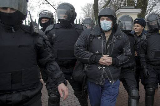 Police officers detain a man during a protest in St. Petersburg, Russia, Sunday, Nov. 5, 2017. Scores of people have been arrested in St. Petersburg and Moscow while trying to gather for an unauthorized protest demonstration called for by an extreme nationalist group.