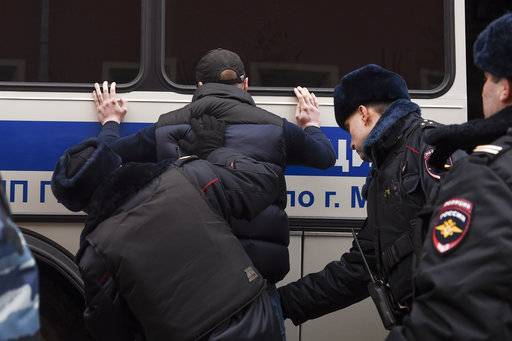 Police officers search a man during a protest in Moscow, Russia, Sunday, Nov. 5, 2017. Scores of people have been arrested in the center of Moscow while trying to gather for an unauthorized protest demonstration called for by an extreme nationalist group.