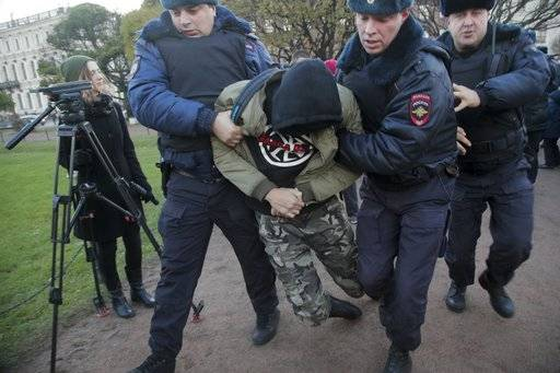 Police officers detain a man during a protest in St.Petersburg, Russia, Sunday, Nov. 5, 2017. Scores of people have been arrested in St. Petersburg and Moscow while trying to gather for an unauthorized protest demonstration called for by an extreme nationalist group.