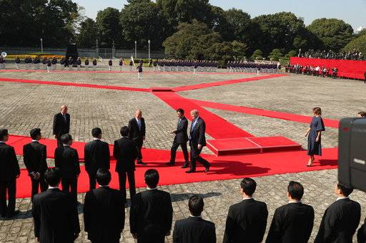 President Donald Trump, center, is escorted by Japanese Prime Minister Shinzo Abe, during the honor guard ceremony at the Akasaka Palace, Monday, Nov. 6, 2017, in Tokyo. Trump is on a five country trip through Asia traveling to Japan, South Korea, China, Vietnam and the Philippines.