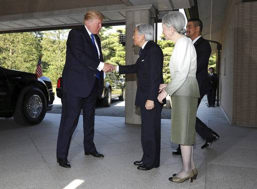 U.S. President Donald Trump, left, is greeted by Emperor Akihito, center, and Empress Michiko upon his arrival at the Imperial Palace in Tokyo Monday, Nov. 6, 2017.