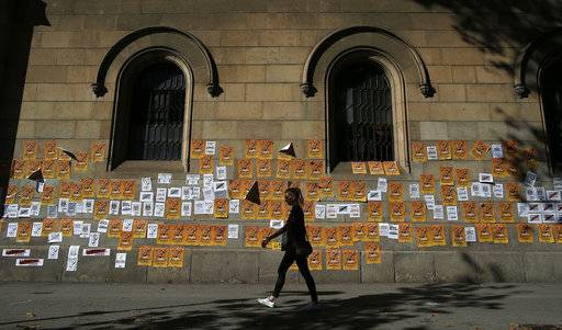 "A woman walks past a wall with banners that read in Catalan: ""Freedom for the Political Prisoners"" during a protest against the decision of a judge to jail ex-members of the Catalan government at the University square in Barcelona, Spain, Sunday, Nov. 5, 2017. A Spanish judge issued an international arrest warrant on Friday for former members of the Catalan Cabinet who were last seen in Brussels, including the ousted separatist leader Carles Puigdemont, who said he was prepared to run for his old job even while battling extradition in Belgium."