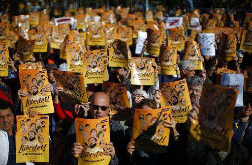 "Demonstrators holding banners that read in Catalan: ""Freedom for the Political Prisoners"", gather during a protest against the decision of a judge to jail ex-members of the Catalan government at the University square in Barcelona, Spain, Sunday, Nov. 5, 2017. A Spanish judge issued an international arrest warrant on Friday for former members of the Catalan Cabinet who were last seen in Brussels, including the ousted separatist leader Carles Puigdemont, who said he was prepared to run for his old job even while battling extradition in Belgium."