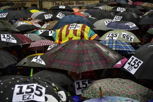 People shelter under umbrellas, at Plaza Consistorial square during a protest against Article 155 of the Constitution, which gives the central government extra powers to re-establish the rule of law in a region, in Pamplona, northern Spain, Spain, Sunday, Nov. 5, 2017.