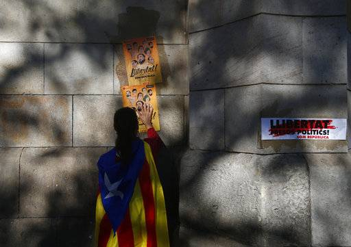 "A woman with a 'Estelada', the pro-independence Catalan flag around her shoulders pastes a banner on a wall reading in Catalan ""freedom for the political prisoners"" during protest against the decision of a judge to jail ex-members of the Catalan government at the University square in Barcelona, Spain, Sunday, Nov. 5, 2017. A Spanish judge issued an international arrest warrant on Friday for former members of the Catalan Cabinet who were last seen in Brussels, including the ousted separatist leader Carles Puigdemont, who said he was prepared to run for his old job even while battling extradition in Belgium."