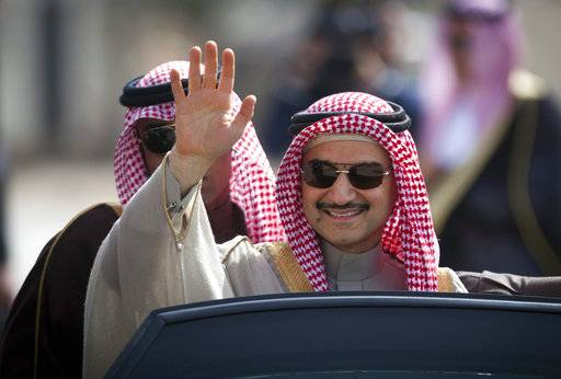 FILE - In this Feb. 4, 2014 file photo, Saudi billionaire Prince Alwaleed bin Talal, waves as he arrives at the headquarters of Palestinian President Mahmoud Abbas in the West Bank city of Ramallah.  Saudi Arabia has arrested dozens of princes and former government ministers, including a well-known billionaire with extensive holdings in Western companies, as part of a sweeping anti-corruption probe, further cementing King Salman and his crown prince son's control of the kingdom. A high-level employee at Prince Alwaleed bin Talal's Kingdom Holding Company told The Associated Press that the royal was among those detained overnight Saturday, Nov. 4, 2017.