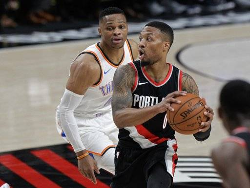 Portland Trail Blazers guard Damian Lillard, right, looks to pass as Oklahoma City Thunder guard Russell Westbrook defends during the first half of an NBA basketball game in Portland, Ore., Sunday, Nov. 5, 2017.