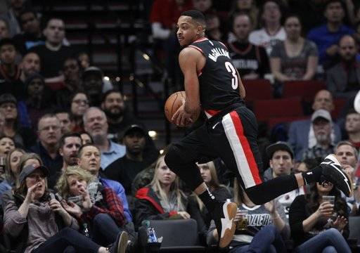 Portland Trail Blazers guard CJ McCollum saves a ball from going out of bounds against the Oklahoma City Thunder during the first half of an NBA basketball game in Portland, Ore., Sunday, Nov. 5, 2017.