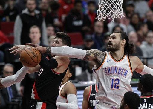 Portland Trail Blazers center Jusuf Nurkic, left, and Oklahoma City Thunder center Steven Adams reach for a rebound during the first half of an NBA basketball game in Portland, Ore., Sunday, Nov. 5, 2017.