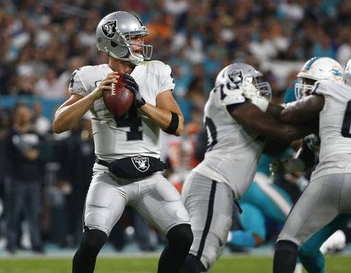 Oakland Raiders quarterback Derek Carr (4) looks to pass, during the first half of an NFL football game against the Miami Dolphins, Sunday, Nov. 5, 2017, in Miami Gardens, Fla.