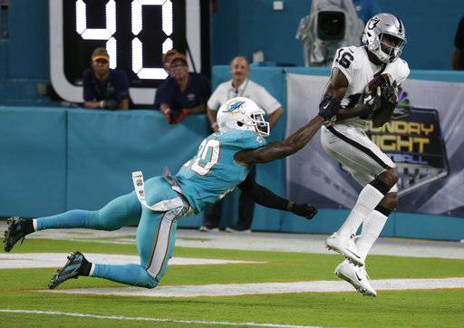 Oakland Raiders wide receiver Johnny Holton (16) grabs a touchdown pass as Miami Dolphins free safety Reshad Jones (20) attempts to defend, during the first half of an NFL football game, Sunday, Nov. 5, 2017, in Miami Gardens, Fla.