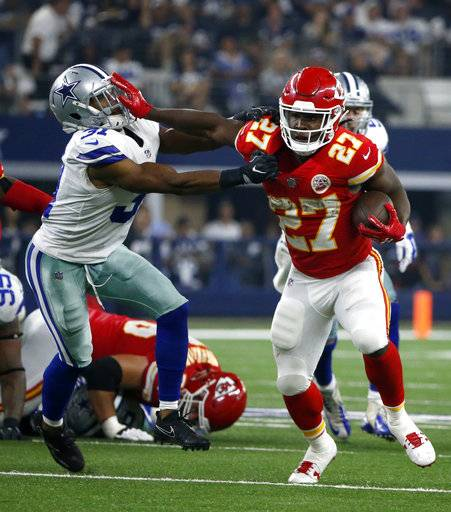 Kansas City Chiefs running back Kareem Hunt (27) fights off a tackle attempt by Dallas Cowboys safety Byron Jones (31) in the second half of an NFL football game, Sunday, Nov. 5, 2017, in Arlington, Texas.