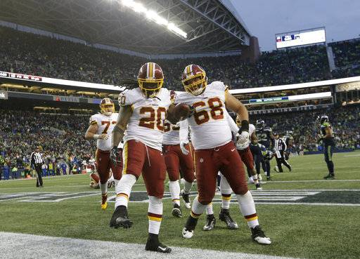 Washington Redskins running back Rob Kelley (20) celebrates with offensive guard Tyler Catalina (68) after Kelley scored a touchdown in the second half of an NFL football game against the Seattle Seahawks, Sunday, Nov. 5, 2017, in Seattle. The Redskins won 17-14.