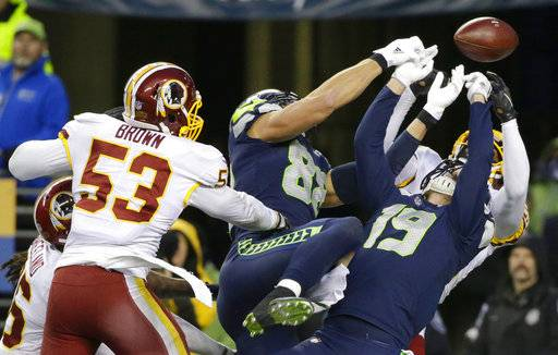 Washington Redskins free safety DeAngelo Hall, right obscured, and inside linebacker Zach Brown (53) break up a pass as Seattle Seahawks tight end Jimmy Graham (88) and wide receiver Tanner McEvoy (19) reach for the ball late in the second half of an NFL football game, Sunday, Nov. 5, 2017, in Seattle. Washington won 17-14.
