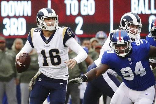 Los Angeles Rams' Jared Goff (16) looks to pass during the first half of an NFL football game as New York Giants' Dalvin Tomlinson (94) closes in Sunday, Nov. 5, 2017, in East Rutherford, N.J. Goff threw a pass for a touchdown to Tyler Higbee on the play.