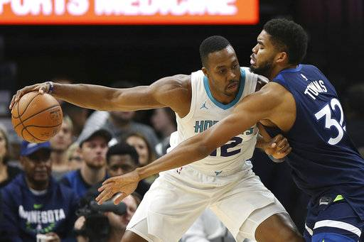 Charlotte Hornets center Dwight Howard (12) protects the ball from Minnesota Timberwolves center Karl-Anthony Towns (32) in the first half of an NBA basketball game, Sunday, Nov. 5, 2017, in Minneapolis.