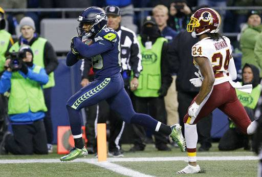 Seattle Seahawks wide receiver Doug Baldwin, left, runs in for a touchdown ahead of Washington Redskins cornerback Josh Norman, right, in the second half of an NFL football game, Sunday, Nov. 5, 2017, in Seattle.