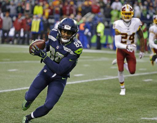 Seattle Seahawks wide receiver Doug Baldwin, left, runs in for a touchdown ahead of Washington Redskins cornerback Josh Norman, right, after making a catch in the second half of an NFL football game, Sunday, Nov. 5, 2017, in Seattle.