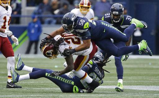 Washington Redskins running back Rob Kelley is brought down by Seattle Seahawks outside linebacker K.J. Wright (50) and cornerback Richard Sherman (25) as strong safety Kam Chancellor (31) looks on in the second half of an NFL football game, Sunday, Nov. 5, 2017, in Seattle.