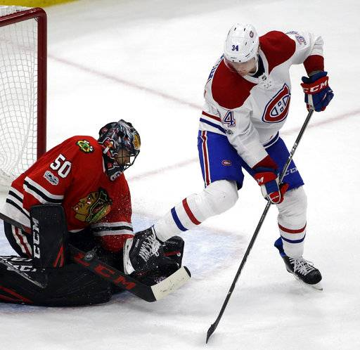 Chicago Blackhawks goalie Corey Crawford, left, blocks a shot by Montreal Canadiens right wing Michael McCarron during the second period of an NHL hockey game, Sunday, Nov. 5, 2017, in Chicago.