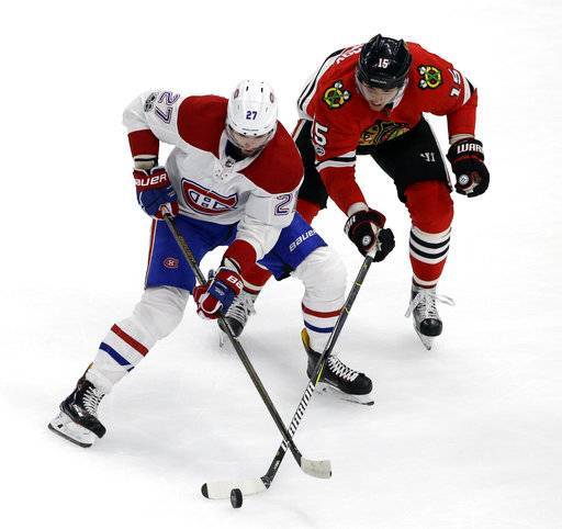 Montreal Canadiens left wing Alex Galchenyuk, left, and Chicago Blackhawks center Artem Anisimov battle for the puck during the first period of an NHL hockey game, Sunday, Nov. 5, 2017, in Chicago.