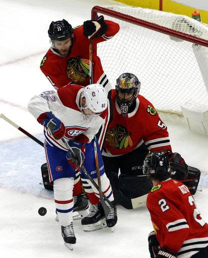 Montreal Canadiens left wing Arthur Lehkonen (62) shoots against Chicago Blackhawks goalie Corey Crawford and defenseman Cody Franson during the first period of an NHL hockey game, Sunday, Nov. 5, 2017, in Chicago.