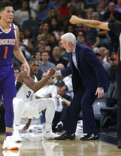 San Antonio Spurs head coach Gregg Popovich helps up Brandon Paul after he draw a charge against Phoenix Suns Devin Booker, left, during the first half of an NBA game on Sunday, Nov. 5, 2017 in San Antonio.