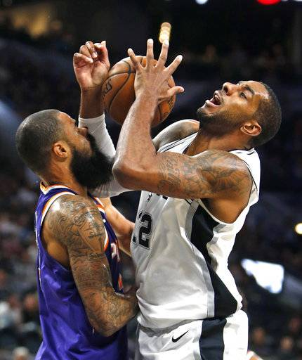 San Antonio Spurs' LaMarcus Aldridge(12) of the San Antonio Spurs is fouled by Phoenix Suns' Tyson Chandlerin a NBA game on Sunday, Nov. 5, 2017 in San Antonio.