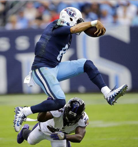 Tennessee Titans quarterback Marcus Mariota (8) leaps over Baltimore Ravens strong safety Tony Jefferson (23) in the first half of an NFL football game Sunday, Nov. 5, 2017, in Nashville, Tenn.