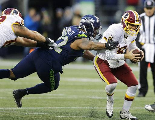 Washington Redskins quarterback Kirk Cousins, right, scrambles away from a tackle attempt by Seattle Seahawks defensive end Michael Bennett, left, in the second half of an NFL football game, Sunday, Nov. 5, 2017, in Seattle.